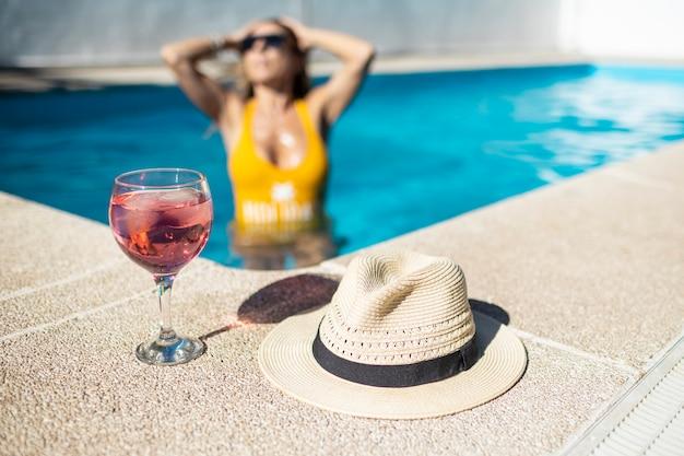 Czerwony koktajl i kapelusz przeciwko nieostre kobiecie w żółtym stroju kąpielowym w niebieskim basenie