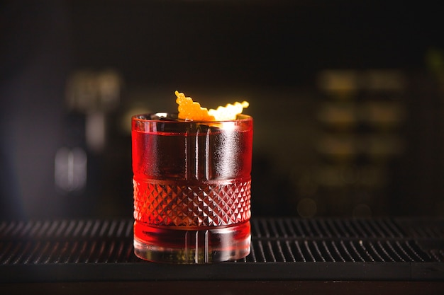 Czerwony koktajl na barze w pięknym szkle z pomarańczową skórką.