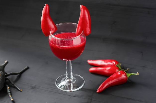 Czerwony koktajl na halloween ozdobiony diabelskimi rogami papryczki chili. na czarnej powierzchni