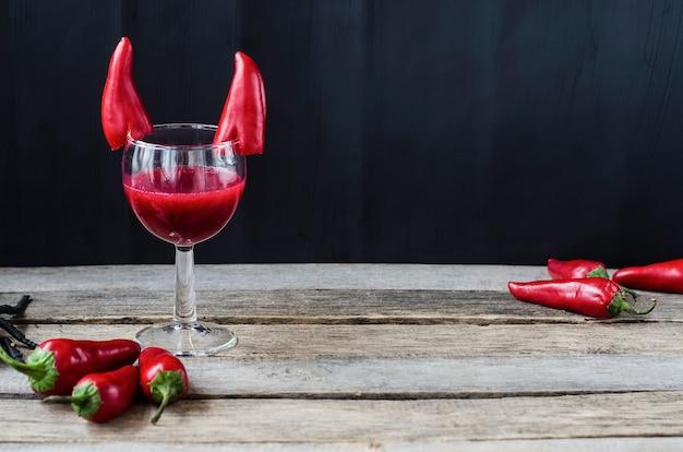 Czerwony koktajl na halloween, udekorowany papryczką chili z diabelskimi rogami. na powierzchni drewnianej