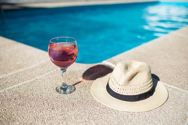 Czerwony koktajl w szklanym kubku obok kapelusza na niebieskim basenie z nieskoncentrowaną kobietą cieszącą się