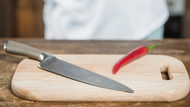 Czerwony korzenny chili pieprz i ostry nóż na ciapanie desce