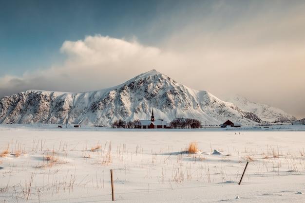 Czerwony kościół parafialny z górą w snowy w flakstad, norwegia