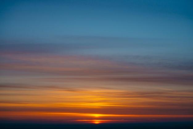 Czerwony krąg słońca wznosi się zza ciemnego horyzontu na różnokolorowych chmurach o ciepłych odcieniach. piękny tło świt na malowniczym obłocznym niebie. słońce w centrum.