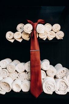 Czerwony krawat wist na tle złożonych białych ręczników w salonie fryzjerskim