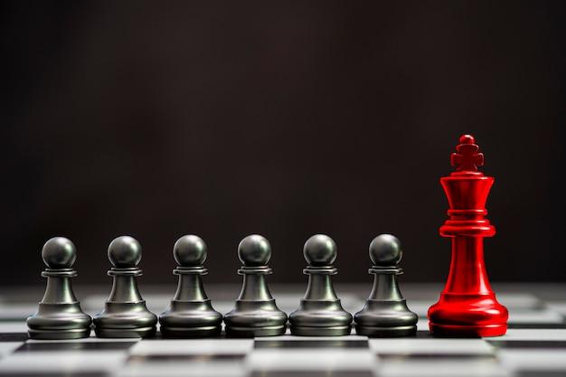 Czerwony król szachy z innymi czarnymi pionkami w szachy dla lidera i innego myślenia. koncepcja przerywa.