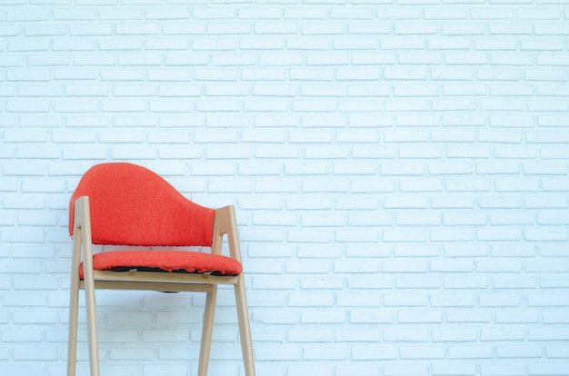 Czerwony krzesło na białym ceglanym tle, nowożytny pokój, kopii przestrzeń.