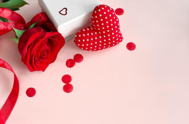 Czerwony kształt serca, pudełko i kwiat czerwonej róży na różowym tle z miejsca na kopię