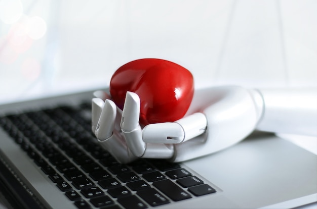 Czerwony kształt serca w ręce robota na klawiaturze laptopa