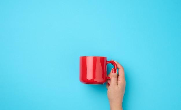 Czerwony kubek ceramiczny w kobiecej dłoni na niebieskim tle, napój i ręka uniesione do góry, przerwa na kawę