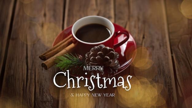 Czerwony kubek do kawy z bożonarodzeniową wiadomością na rustykalnym drewnianym tle