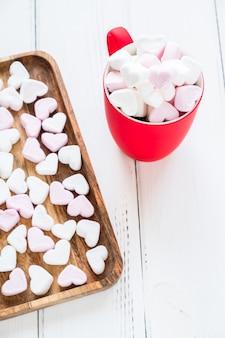 Czerwony kubek gorącego kakao z marshmallows w kształcie serca na białym tle drewnianych