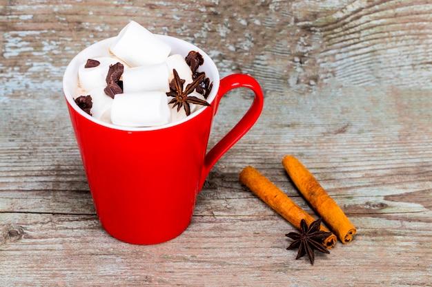 Czerwony kubek gorącego napoju czekoladowego z marshmallows, kawałkami czekolady i cynamonem na drewnianym tle. zimowy czas. koncepcja wakacje, selektywne focus.