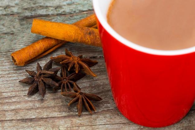 Czerwony kubek gorącego napoju czekoladowego zi cynamonem na drewnianym tle. zimowy czas. koncepcja wakacje, selektywne focus.