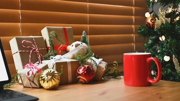 Czerwony kubek gorącego napoju i prezenty świąteczne na drewnianym stole.