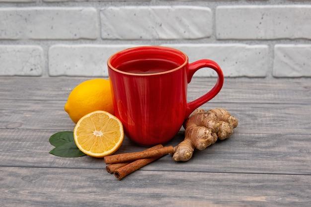 Czerwony kubek gorącej czarnej lub zielonej herbaty z cytryną i imbirem na drewnianym tle. składniki przeciwko grypie i wirusom. medycyna naturalna.