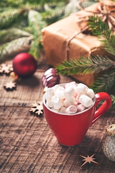 Czerwony kubek gorącej czekolady z gałęziami prawoślazu i jodły, pudełka na tle śniegu zima z śnieżnymi gałęziami na starym drewnianym stole. koncepcja boże narodzenie czy zima.