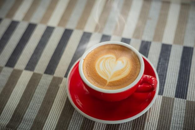 Czerwony kubek, kawa latte w kształcie serca na drewnianym obrusie