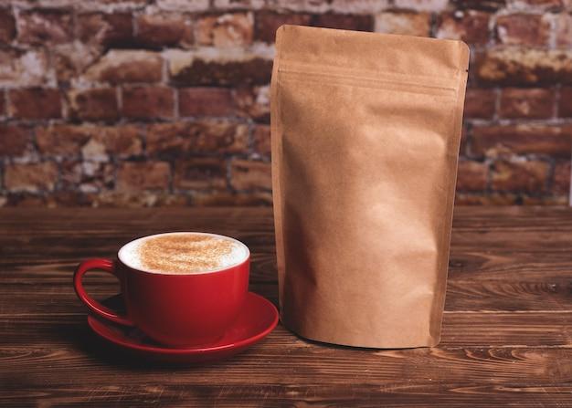 Czerwony kubek kawy i worek z papieru rzemieślniczego na drewnianym stole przy ścianie z cegły