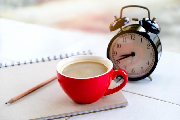 Czerwony kubek kawy jest połączony z czarnym zegarem, z książkami i