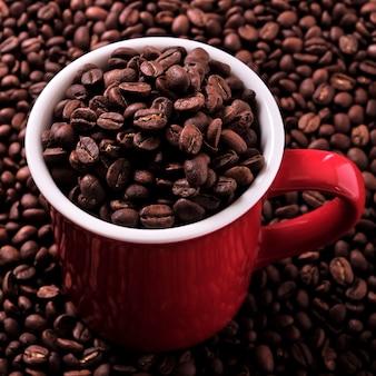 Czerwony kubek kawy wypełniony ziarnami