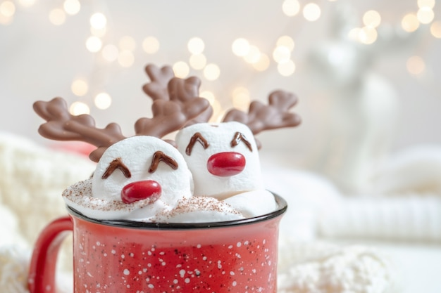 Czerwony kubek z gorącą czekoladą i roztopionym reniferem ptasie mleczko