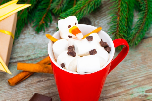 Czerwony kubek z gorącą czekoladą z roztopionym bałwanem z pianki marshmallow.