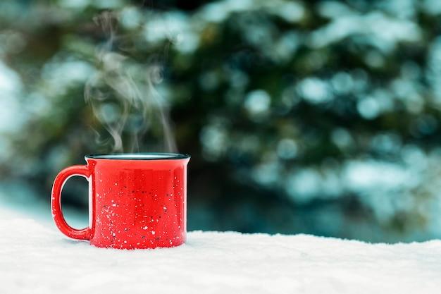 Czerwony kubek z gorącym zimowym napojem (grzane wino, kakao, kawa, herbata) na tle zimowego lasu i śniegu. zimowy nastrój i komfort.