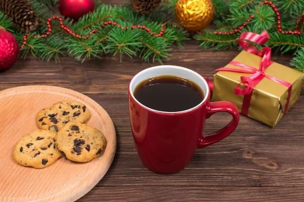 Czerwony kubek z herbatą, kawą z ciasteczkami i piankami na drewnianym stole na tle choinki z dekoracjami świątecznymi.