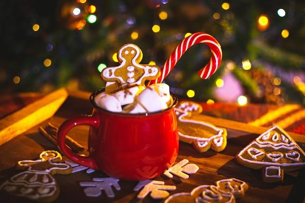 Czerwony kubek z kakao i piankami. piernik domowej roboty. tradycyjne ozdoby świąteczne.