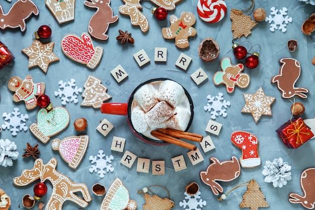 """Czerwony kubek z kakao i piankami, świątecznym piernikiem i napisem """"merry christmas"""" wykonanym drewnianymi literami."""