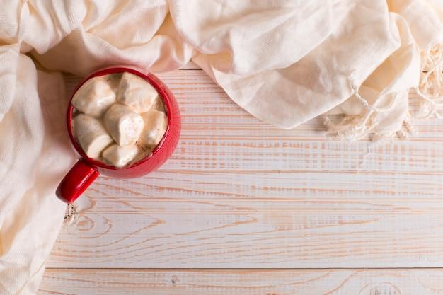 Czerwony kubek z kakao i pianki na tle biały szalik tabeli. jesienny nastrój, napój rozgrzewający. copyspace.