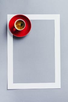 Czerwony kubek z kawą i ramą papieru na klasycznym niebieskim tle