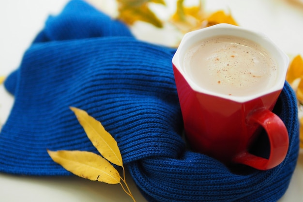 Czerwony kubek z kawą na stole w niebieski szalik z dzianiny i żółte jesienne liście. witam jesień koncepcja. choroby sezonowe