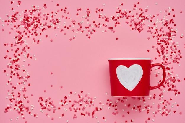 Czerwony kubek z malowanym sercem, cukrowo-czekoladowymi serduszkami na różowym stole. kompozycja płaska świecka. koncepcja walentynki. widok z góry, miejsce na kopię.