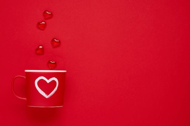 Czerwony kubek z malowanym sercem, cukrowymi i czekoladowymi serduszkami na szkarłatnym lub czerwonym stole. kompozycja płaska świecka. koncepcja walentynki. widok z góry, miejsce na kopię.