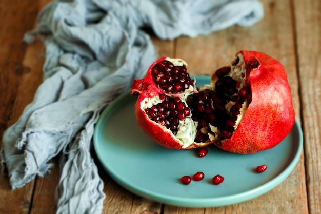 Czerwony, łamany granat na talerzu. jagoda w talerzu na drewnianym stole