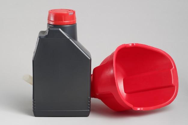 Czerwony lejek i jedna litrowa butelka oleju silnikowego.
