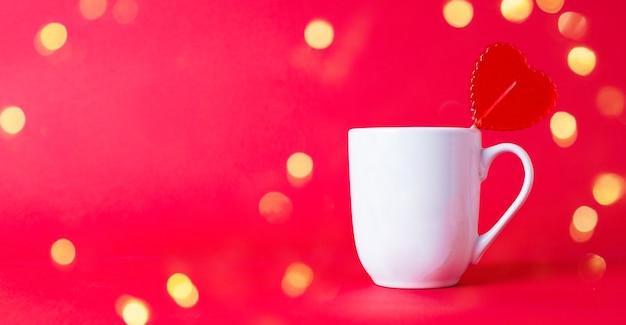 Czerwony lizak w kształcie serduszka w białym kubku ze świątecznym bokeh