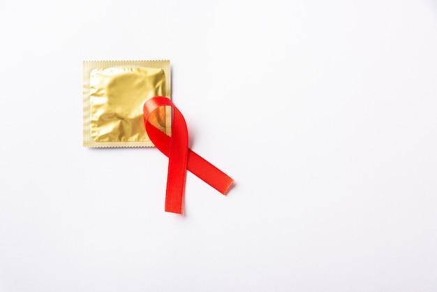 Czerwony łuk wstążka symbol hiv, aids i prezerwatywy