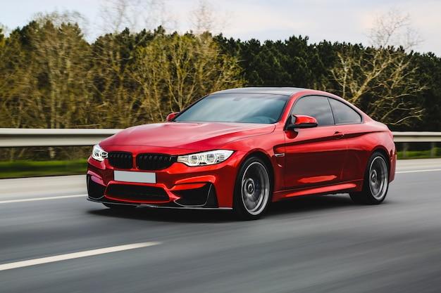 Czerwony luksusowy sedan na drodze.