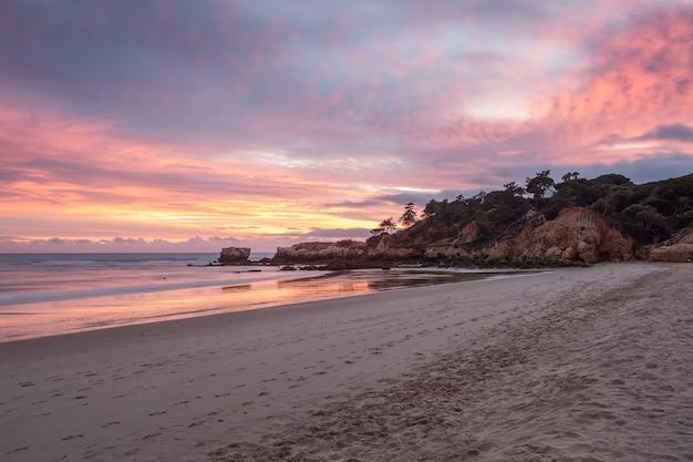 Czerwony magiczny zmierzch na plaży oura w albufeira. portugalia