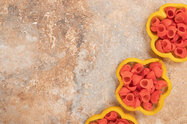 Czerwony makaron w plasterkach papryki na pomarańczowej przestrzeni.