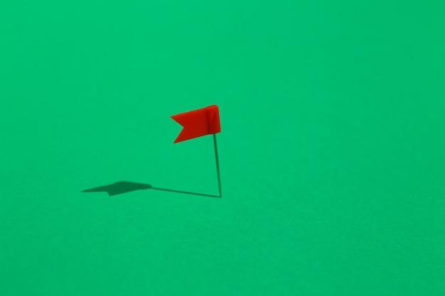 Czerwony mały pin flaga przypięte na zielonym tle. pomysł na biznes .