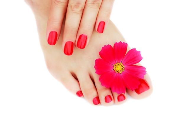 Czerwony manicure i pedicure z kwiatem