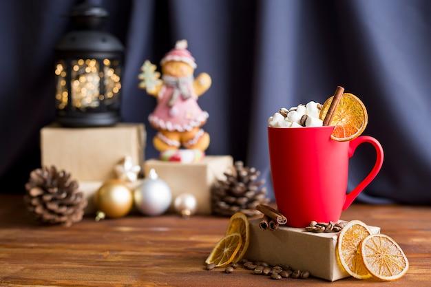 Czerwony matowy kubek z piankami i cynamonem na świątecznym tle