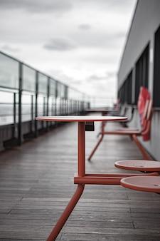Czerwony metalowy stół i krzesła na drewnianym pokładzie