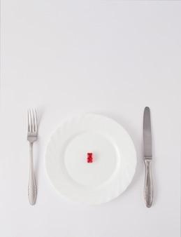Czerwony miś żelkowy podawany na talerzu. minimalna koncepcja kreatywna na białym tle.