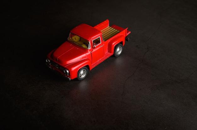 Czerwony model pickupa na czarnej podłodze