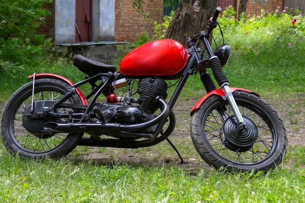 Czerwony motocykl custom na zielonej trawie